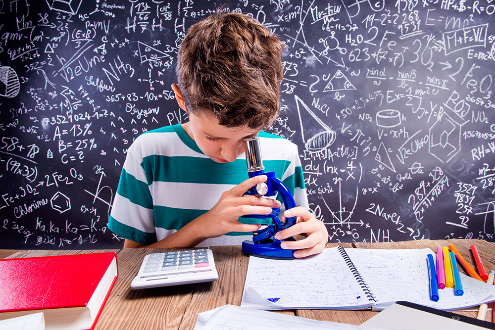 boy looking at microscope