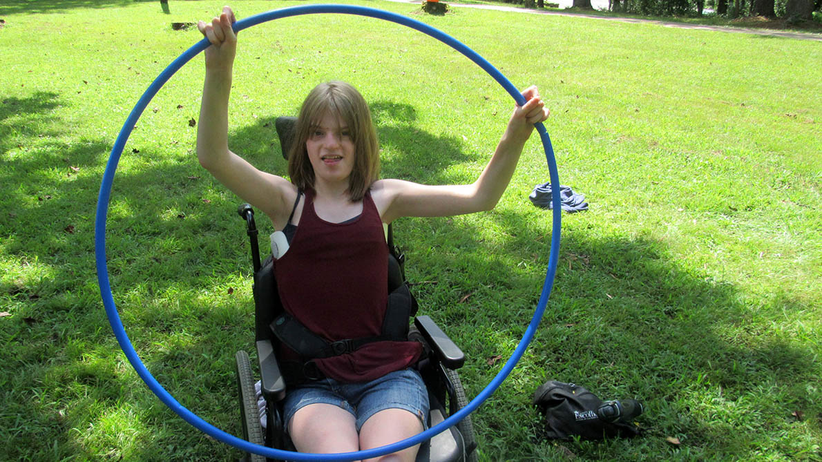 girl in a wheelchair holding a hoop